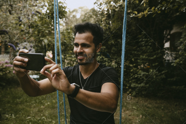 Smiling man photographing through smart phone while sitting on swing in yard