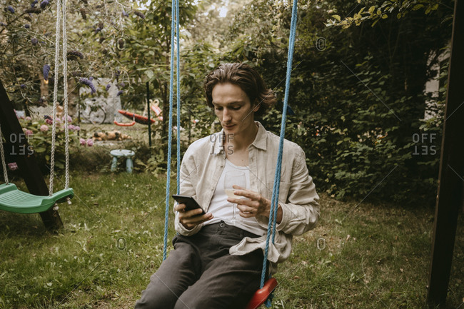 Contemplating man with drink using smart phone while sitting on swing in yard
