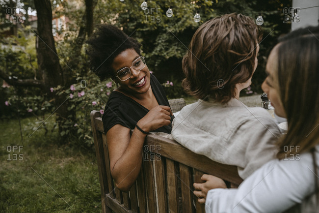 Smiling female talking to young woman behind male partner during social gathering