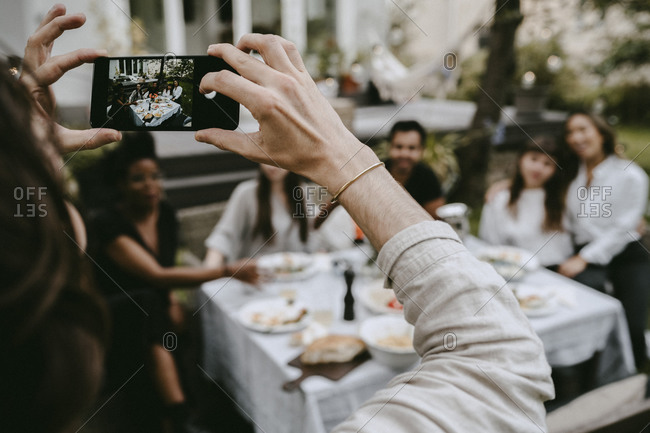 Cropped hand of man photographing through smart phone while friends sitting by table in yard
