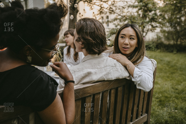 Smiling female talking to friend behind partner during social gathering