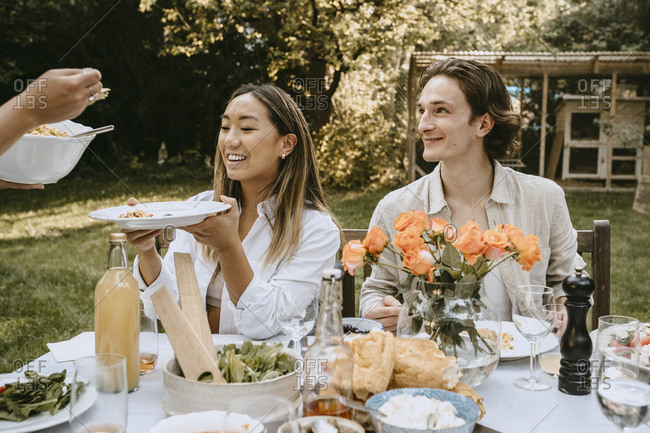 Cropped hand of woman serving food to friends during social gathering