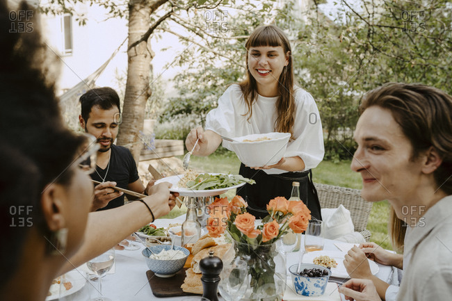 Smiling woman passing food to female friend over table during garden party