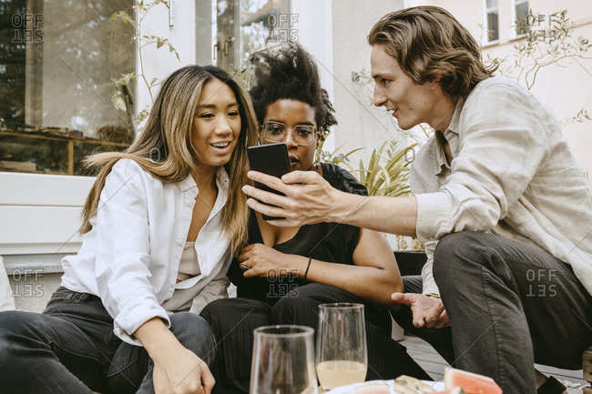 Man showing mobile phone to female friends in backyard