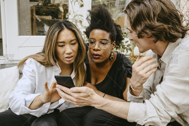 Man showing smart phone to women in backyard