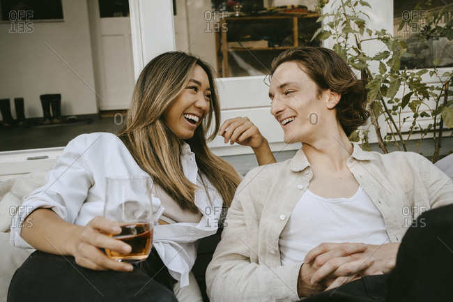 Smiling woman with drinking glass talking to male friend while sitting in backyard