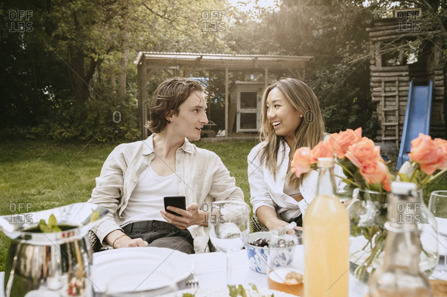 Smiling man with smart phone talking to female friend while sitting at table in backyard