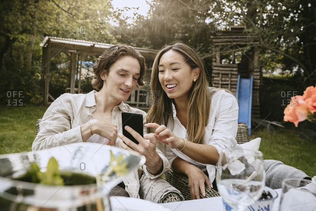 Smiling man showing smart phone to female friend while sitting at table in backyard