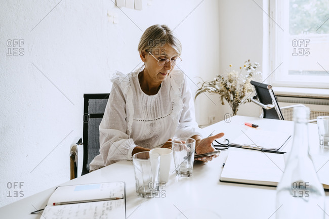 Mature businesswoman using smart phone while sitting at desk in office