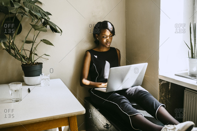 Female entrepreneur using laptop while sitting in office