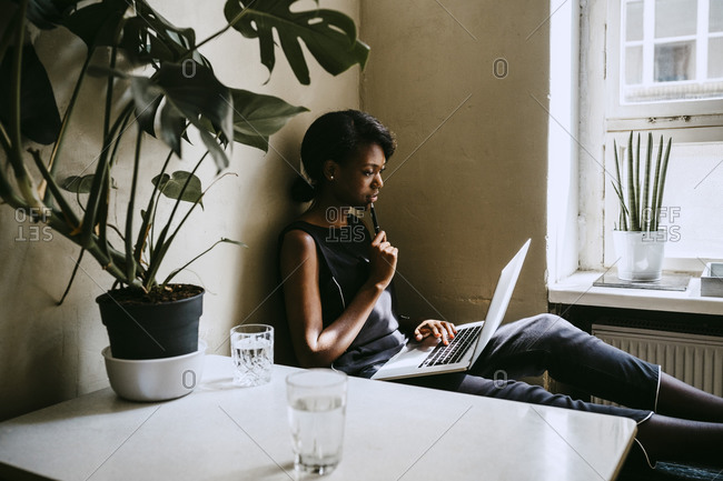 Thoughtful businesswoman using laptop while sitting in office