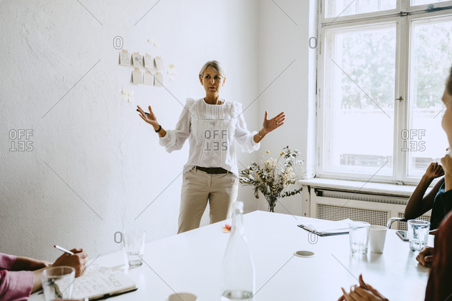 Mature businesswoman explaining colleagues during workshop in office
