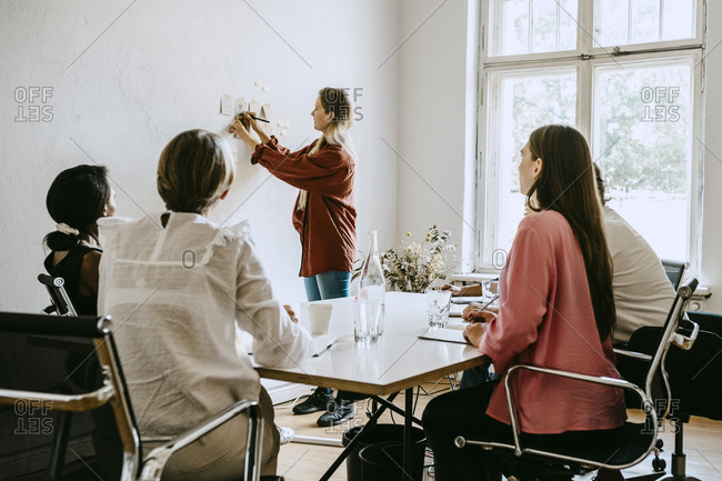 Businesswoman writing on adhesive note while explaining colleagues during seminar in office