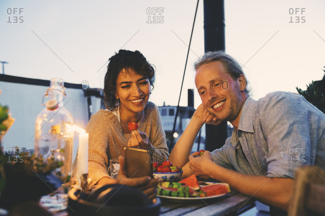Smiling couple taking selfie during candlelight dinner in houseboat during sunset