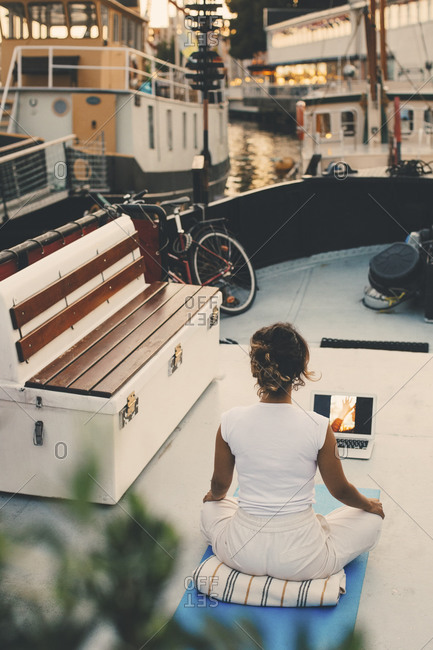 Rear view of woman learning online yoga through laptop in houseboat at harbor