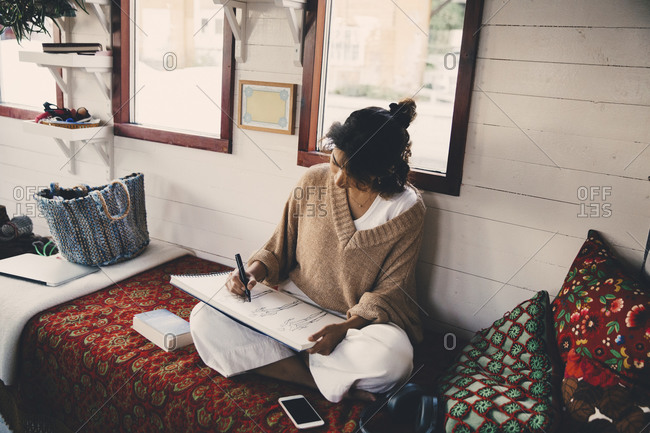 Woman drawing sketch in book at houseboat