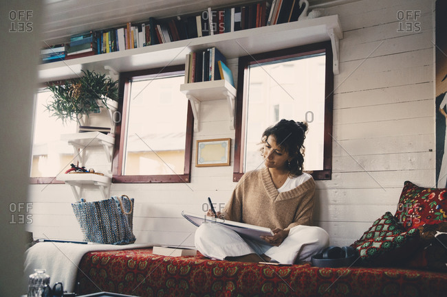 Woman drawing in book while sitting on bed at houseboat