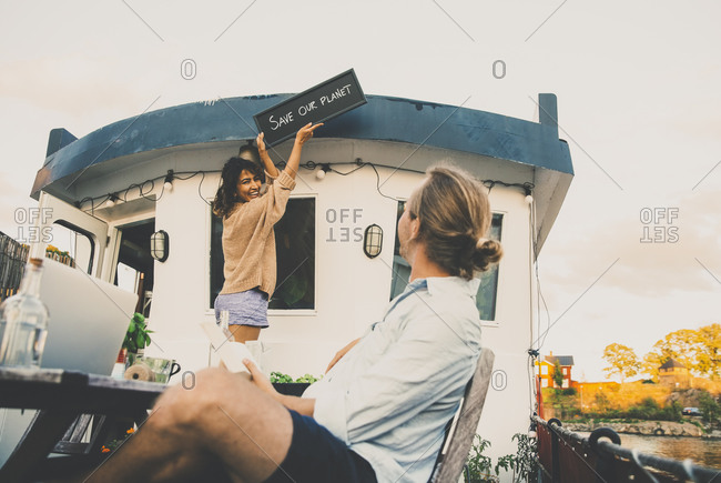 Boyfriend looking at girlfriend mounting placard at houseboat against sky