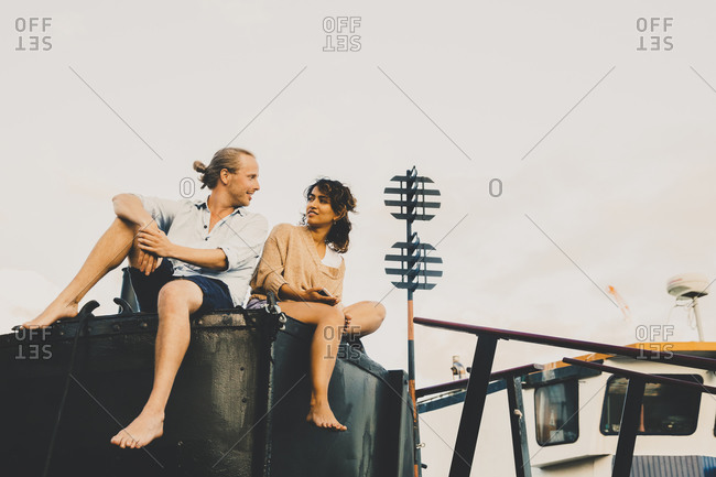 Couple looking at each other while sitting on edge of houseboat against sky