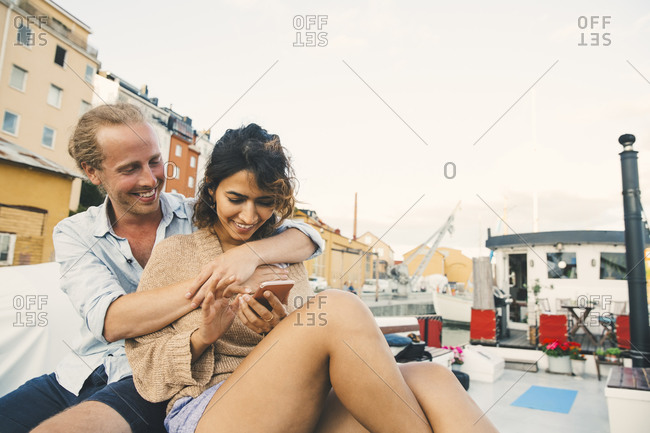 Smiling girlfriend using smart phone while boyfriend embracing in houseboat