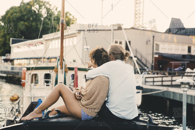 Boyfriend pointing while embracing girlfriend on houseboat at harbor
