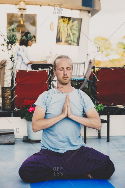 Mid adult man meditating with hands clasped at houseboat
