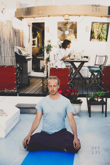 Man doing yoga while businesswoman sitting behind using laptop at houseboat
