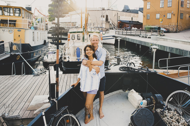 Smiling boyfriend embracing girlfriend while standing in houseboat at harbor