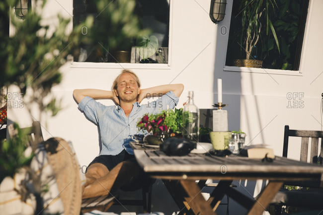 Relaxed man with hands behind head sitting in houseboat