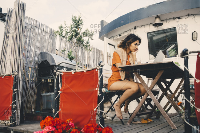 Female entrepreneur working on laptop in houseboat