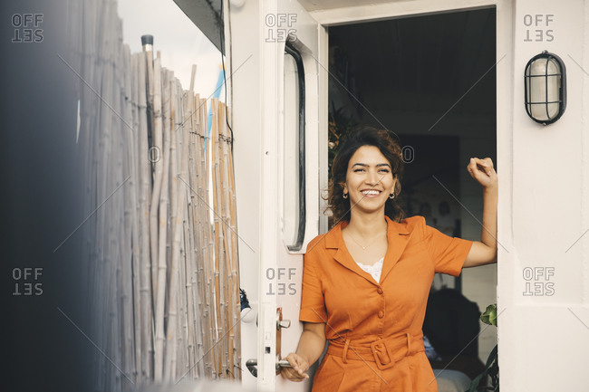 Happy woman looking away while standing at doorway of houseboat