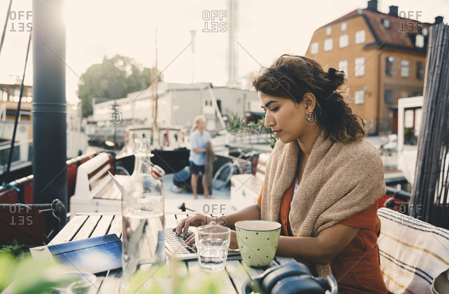 Female entrepreneur using laptop while working remotely in houseboat