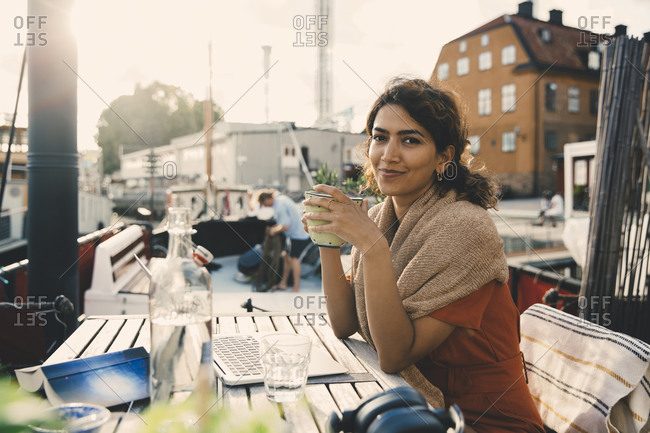 Smiling businesswoman with coffee sitting by laptop at desk in houseboat