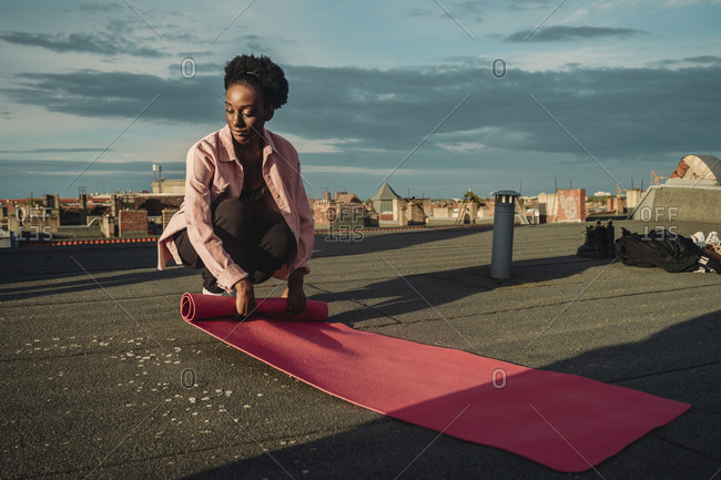 Young female folding exercise mat on rooftop during sunrise
