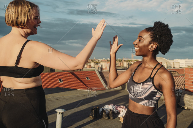 Smiling female friends giving high-five after exercising on rooftop