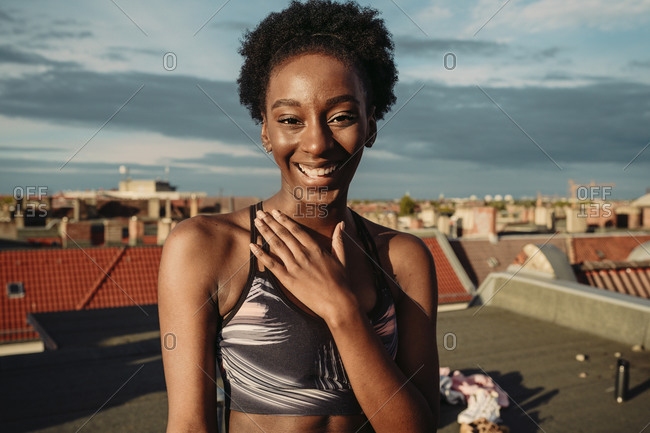 Portrait of happy female in sports clothing standing on rooftop during sunrise