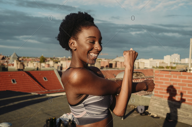 Smiling female stretching on rooftop during sunrise