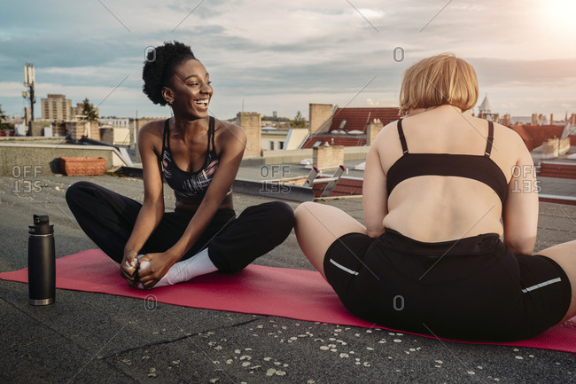 Smiling female friends exercising on rooftop
