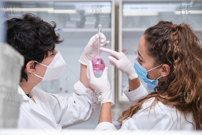 Two young female scientists wearing face masks using a flask. Laboratory research concept.
