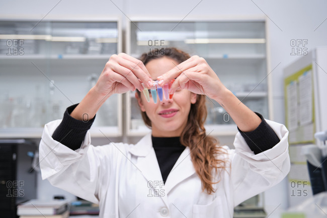Young female scientist smiling with eppendorf tubes in front of her face. Laboratory research concept.