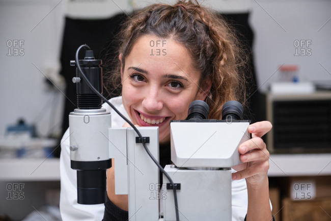 Young female scientist looking at camera and smiling next to a microscope in a laboratory. Laboratory research concept.