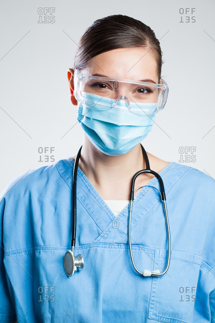 Happy satisfied female doctor wearing protective face mask & safe