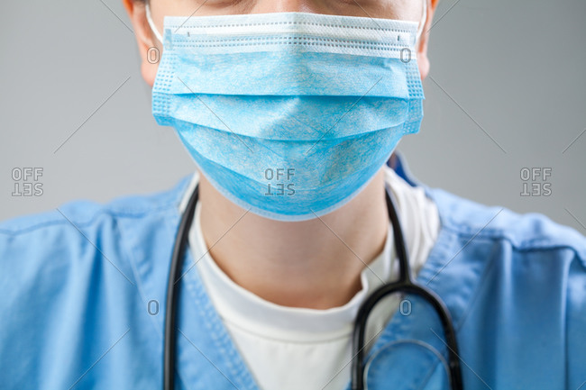 Closeup of doctor in blue uniform wearing blue protective surgical