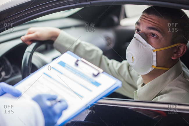 Young man wearing protective face mask in drive-thru Coronavirus