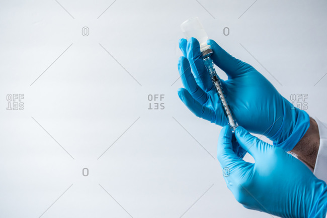 Hands in gloves drawing vaccine into syringe on white background.