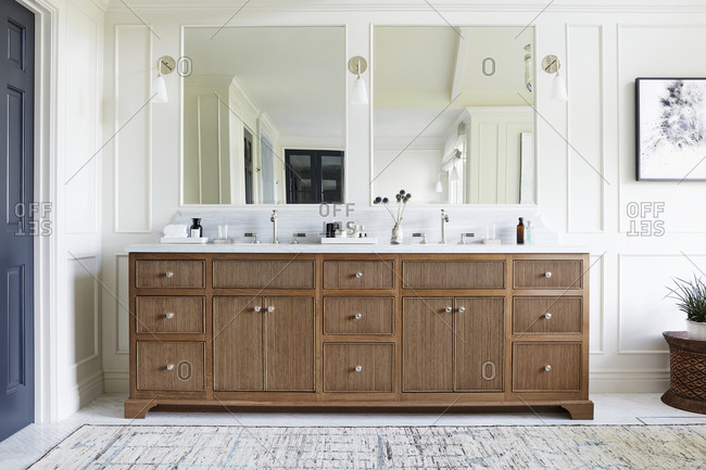 November 5, 2020: Bathroom interior with a large wooden vanity with a white marble top and chrome fixtures