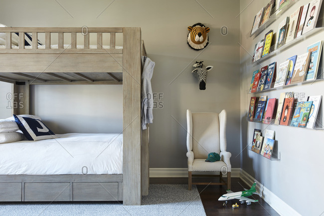 December 9, 2020: Tidy child's room with wooden bunk beds and shelves filled with books on the wall