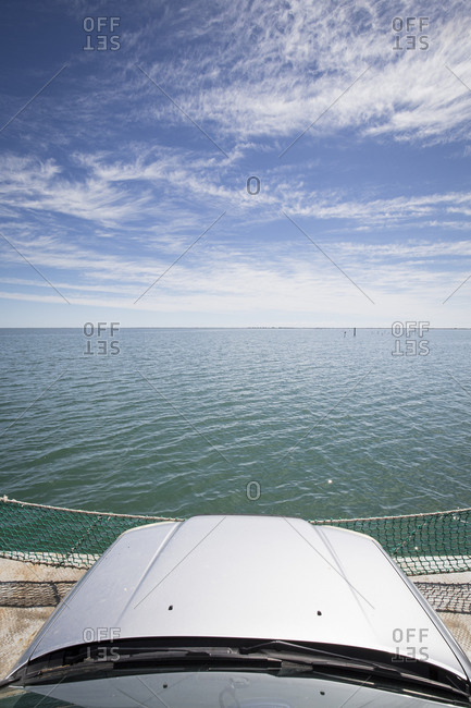 The view atop a car at the front of a private car ferry as it crosses a sound with very little land in sight