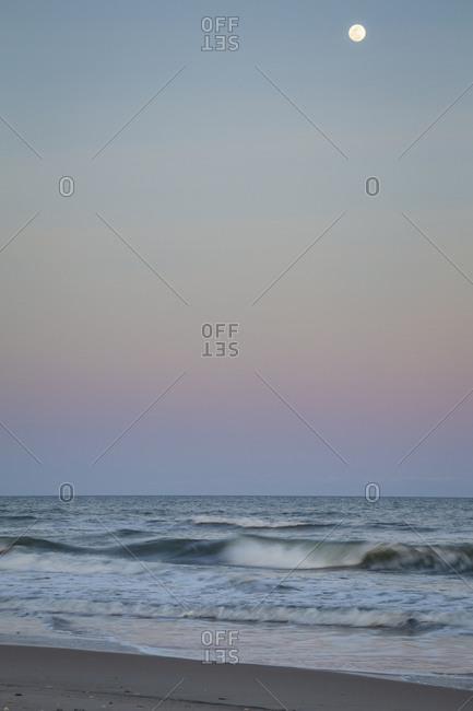 Full moon setting over crashing waves at dawn on Cape Lookout National Seashore, North Core Banks, North Carolina
