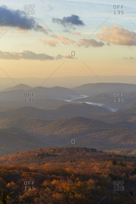Low clouds winding through a valley in the Blue Ridge Mountains at sunrise in Western, North Carolina